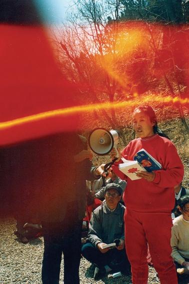"""Ảnh 6: Bức ảnh có chòm sáng hình vòng cung màu đỏ vàng này chụp khi mọi người cùng đọc cuốn sách """"Chuyển Pháp Luân""""."""